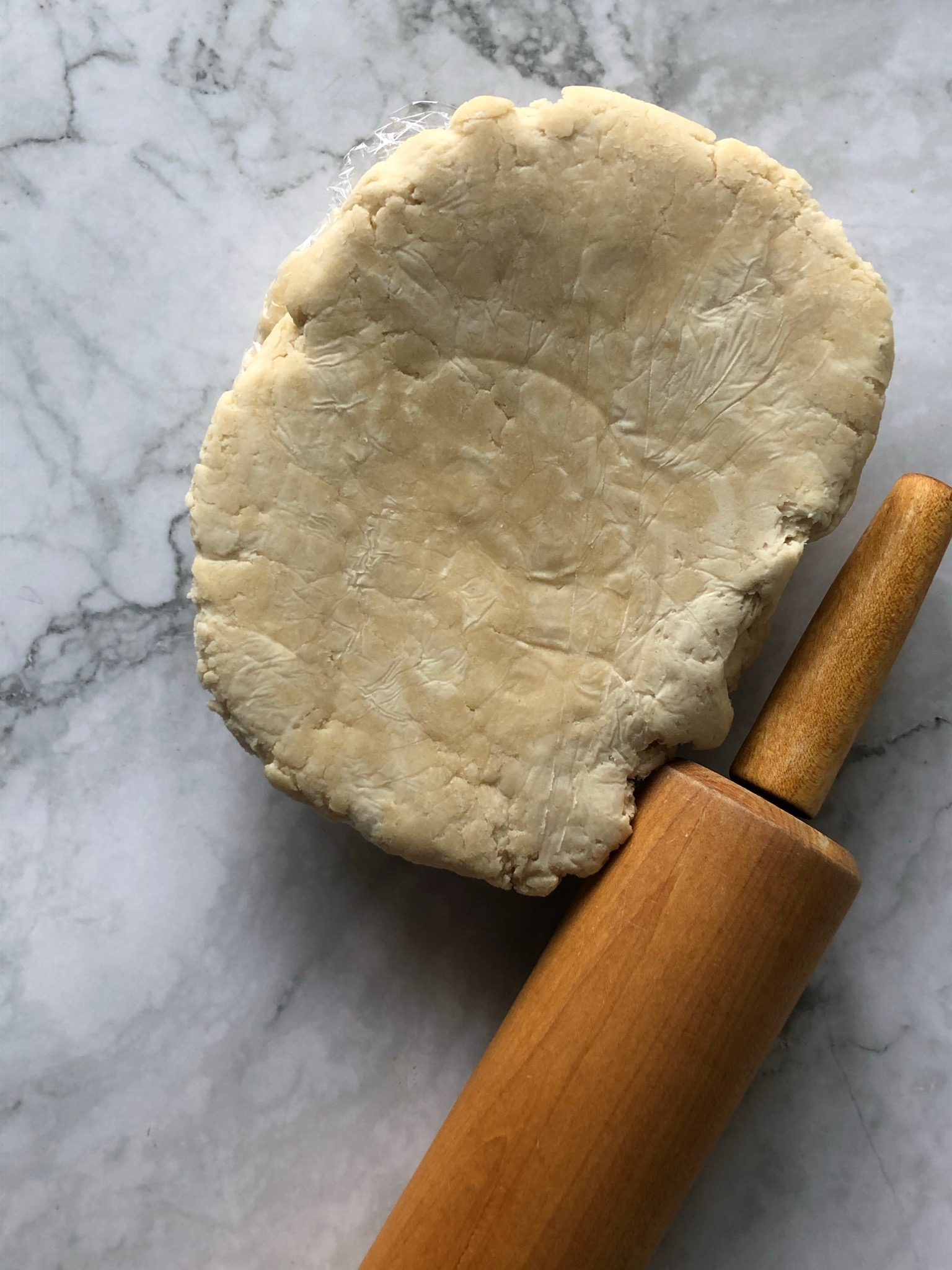 pie dough recipe on marble counter with rolling pin